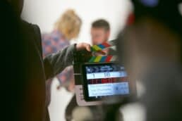 Producer preparing to film a scene. A slap slate is being used.