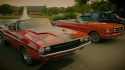 Cherry Red Dodge Challenger and Reddish Orange Ford Mustang sit side by side in front of a water fountain at the September 26th, 2021 Cars & Coffee event in Fitchburg, Wisconsin.